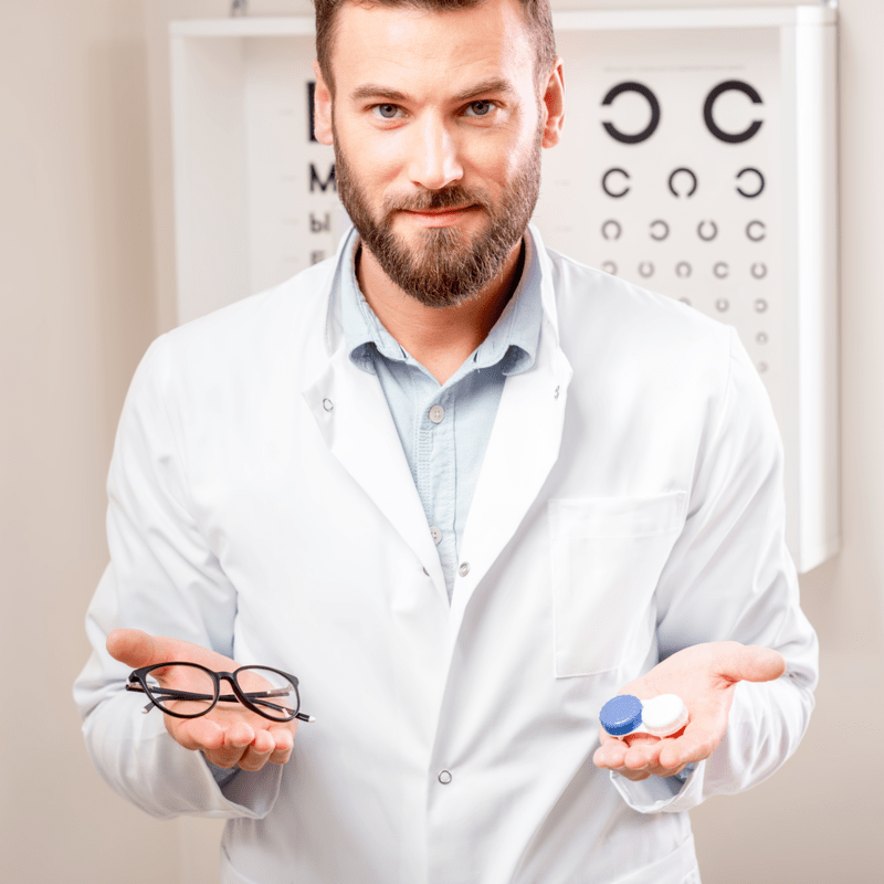 Optometrininkas vienoje rankoje laikantis akinius, kitoje - kontaktinius lęšius ir kontaktinių lęšių dėkliuką