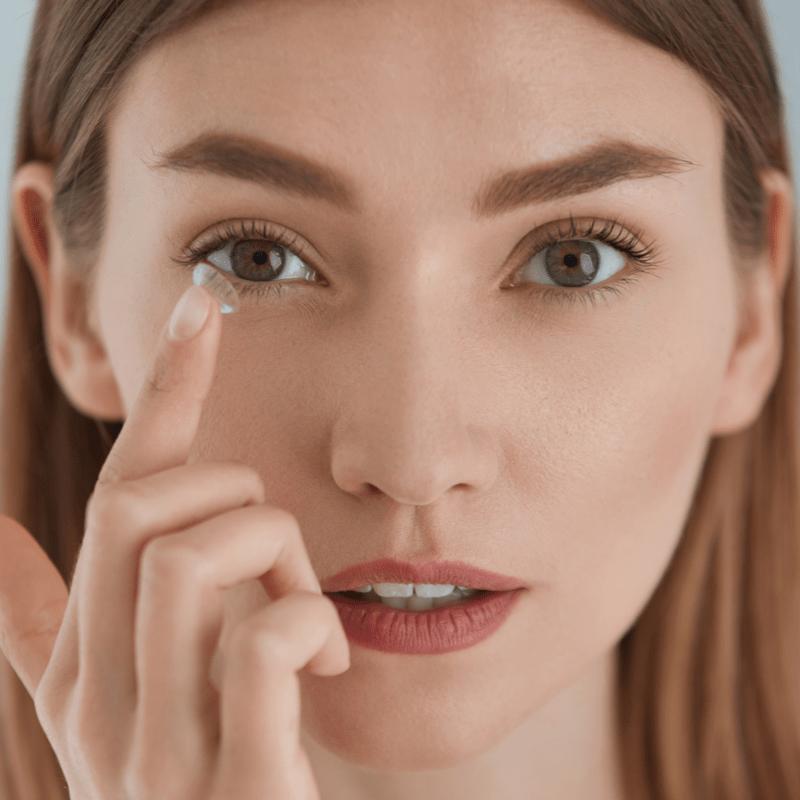 Moteris į akis dedasi kontaktinį lęšį