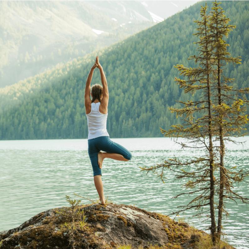 Moteris atlieka jogos pratimus ant akmens ir žvelgia į vandenį ir kalnus