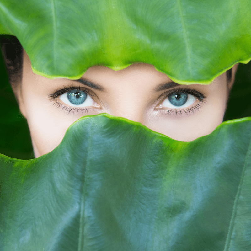 Moteris mėlynomis akimis žvelgia per lapus