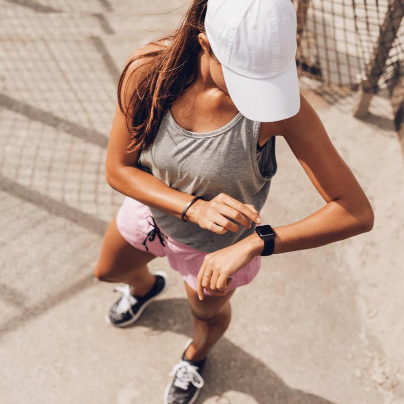 Jauna moteris lauke su išmaniuoju laikrodžiu ant rankos