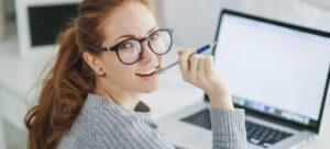 Jauna moteris dėvinti akinius darbui kompiuteriu