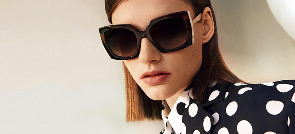 Stilinga jauna moteris su Carolina Herrera 212 akiniais nuo saulės